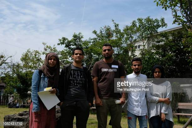 Yemeni refugees Adnan Aldukhaiti Mohammed Abdullah poses for a photo with Tahani Ali Hasan and her family at a garden in front of Jeju Immigration...