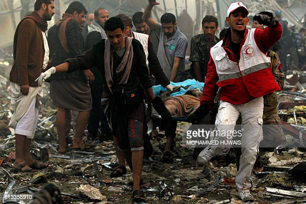 Yemeni rescue workers carry a victim on a stretcher amid the rubble of a destroyed funeral hall building following reported airstrikes by Saudiled...