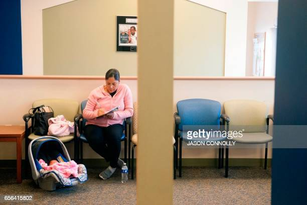 Yemeni Rodriquez fills out paperwork prior to a checkup for her five day old daughter Isabella Prado at Inner City Health Center in Denver Colorado...