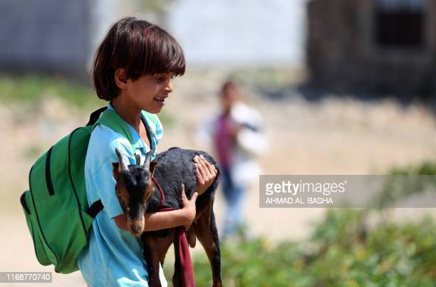 Yemeni school boy holds his goat as he arrives to attend an open-air class at a unfinished school on September 16, 2019 in the southwestern Yemeni...