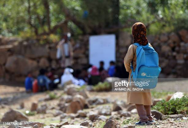 Yemeni school children attend an open-air class under a tree near their unfinished school on September 16, 2019 in the southwestern Yemeni village of...