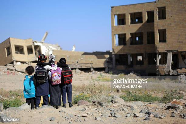TOPSHOT Yemeni school girls look at a school on March 16 that was damaged in an air strike in the southern Yemeni city of Taez The conflict in Yemen...