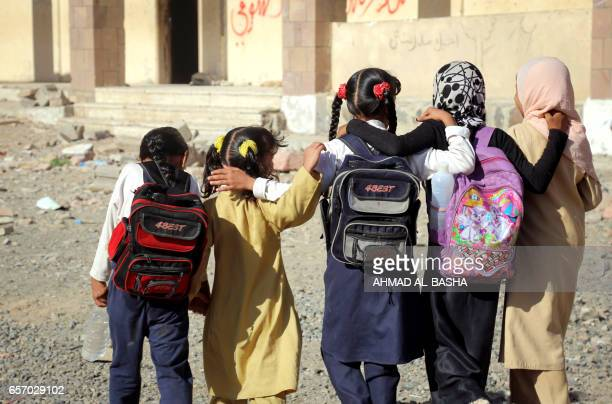 Yemeni school girls walk outside a school on March 16 that was damaged in an air strike in the southern Yemeni city of Taez The conflict in Yemen...