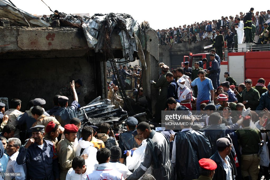 Yemeni security forces and rescue teams rush to the scene of a military plane crash in Sanaa on November 21, 2012, in which 10 people including the pilot were killed as the Antonov jet tried to make an emergency landing when an engine failed, Yemen's defence ministry and an airport source said. The plane crashed in the Yemeni capital's northern neighbourhood of al-Hassaba while trying to land at an air base near Sanaa's main airport.