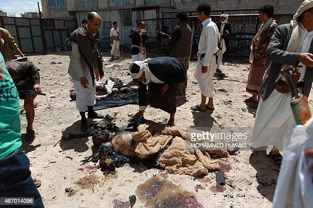Yemeni security forces and Shiite Huthi militiamen stand next to charred bodies following a bomb explosion at the Badr mosque in southern Sanaa on...