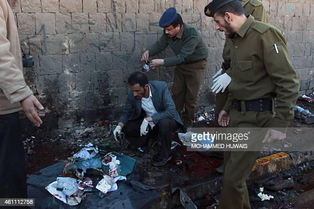 Yemeni security forces collect evidence at the site of a car bomb explosion outside the police academy in Sanaa on January 7 2015 The attack struck...