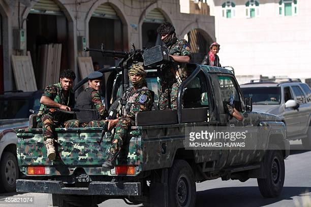 Yemeni security forces escort a convoy transporting suspected alQaeda militants as they arrive at a court on December 2 2014 in the Yemeni capital...