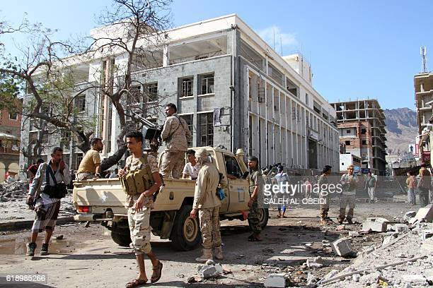 Yemeni security forces gather at the site where a suicide car bomb exploded next to the central bank in Yemen's second city Aden on October 29 2016 A...