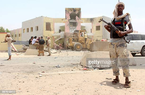 Yemeni security forces stand guard at the site of a suicide car bombing claimed by the Islamic State group on August 29 2016 at an army recruitment...