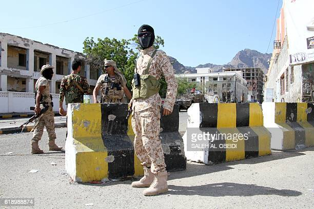 Yemeni security forces stand guard at the site where a suicide car bomb exploded next to the central bank in Yemen's second city Aden on October 29...