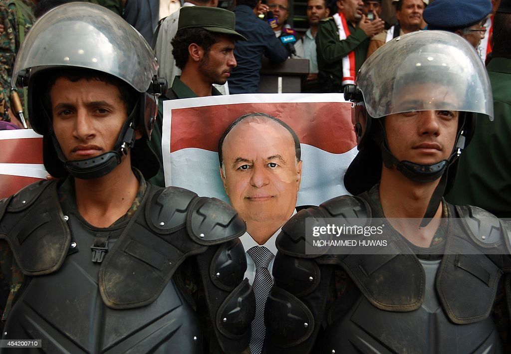 Yemeni security forces stand guard in front of a poster bearing the portrait of President Abd-Rabbu Mansour Hadi during a pro-government demonstration on August 26, 2014, in the Yemeni capital Sanaa. Rival protests stoked up tension in Yemeni capital Sanaa on August 24, as a presidential negotiating team abandoned talks with Shiite rebels, accusing them of seeking to ignite a war.