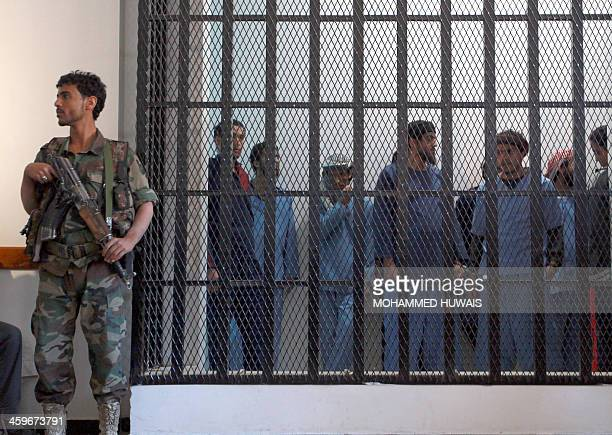 A Yemeni security officer guards prisoners at a court during the sentencing of nine suspects to between two and 10 years in prison for belonging to...