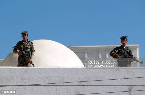 Yemeni security stand guard on the roof of the court house in the capital Sanaa during the sentencing of nine suspects to between two and 10 years in...