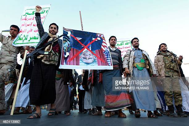 Yemeni Shiite supporters of the Huthi movement carry an upside down portrait of US President Barack Obama bearing a red cross over it during a march...