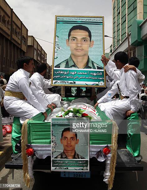 Yemeni Shiites sit at the back of a truck near a portrait and the coffin of one of the 13 fellow Shiite who were killed in the weekend clashes with...