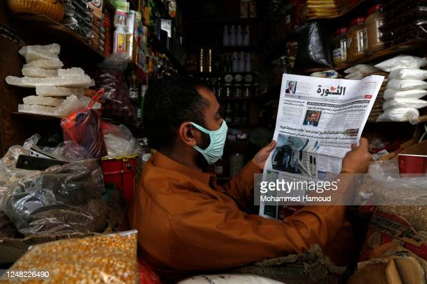 Yemeni shopper wears a protective face mask as a precautionary measure against the coronavirus' spread, reads a local newspaper while waiting for...