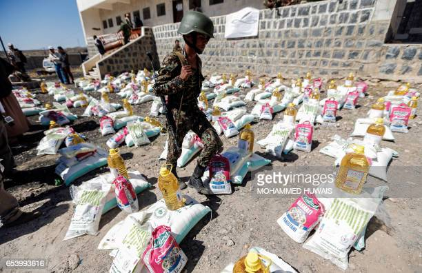 A Yemeni soldier loyal to the Shiite Houthi movement walks next to humanitarian aid supplies given by the Russian humanitarian relief mission in a...