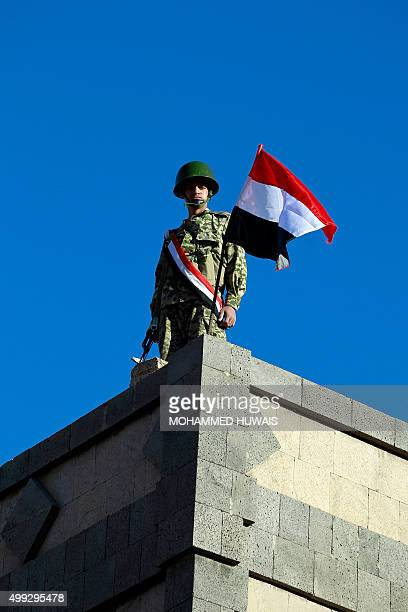A Yemeni soldier loyal to the ShiiteHuthi movement stands on a roof during a rally commemorating the anniversary of the independence of South Yemen...