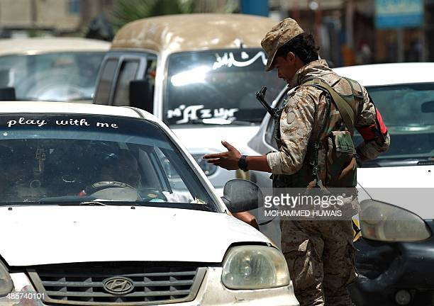 A Yemeni soldier speaks to a driver in a vehicle in the capital Sanaa on April 20 as passing vehicles are checked following the authority's...
