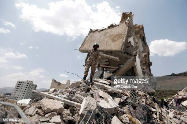 Yemeni soldier stands on the debris of a house hit in an air strike on a residential district in the capital Sanaa on August 26 2017 Children were...