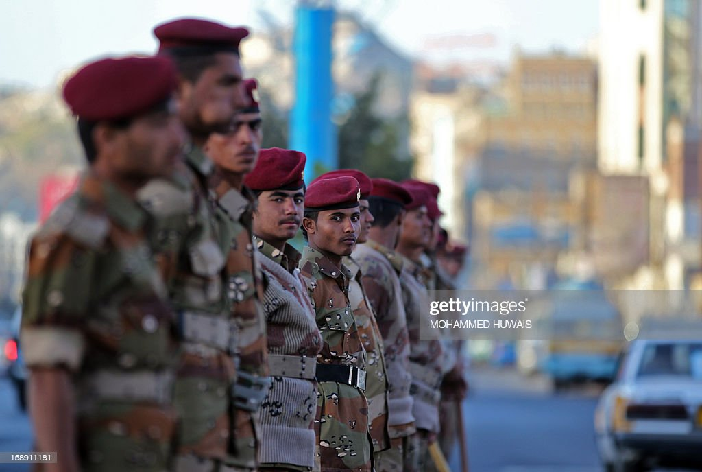 Yemeni soldiers stand guard near the residence of Yemen's President Abdrabuh Mansur Hadi's in Sanaa as protestors demonstrate nearby demanding for a quicker implementation of the President's latest orders to restructure Yemen's military on January 3, 2013.