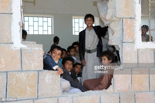 TOPSHOT Yemeni students look out of a hole in the wall of a classroom that was damaged in the country's ongoing conflict between the Saudiled Arab...