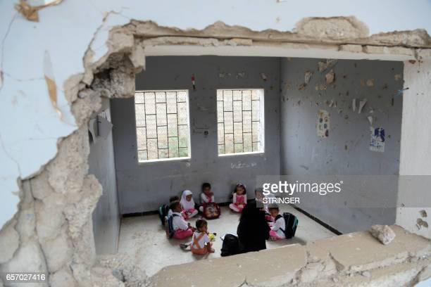 TOPSHOT Yemeni students study in a classroom in the Yemeni port city of Hodeidah on March 15 which was damaged in the country's ongoing conflict...