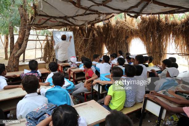 Yemeni students study in a makeshift classroom in the Yemeni port city of Hodeidah on March 15 after their school was damaged in the country's...