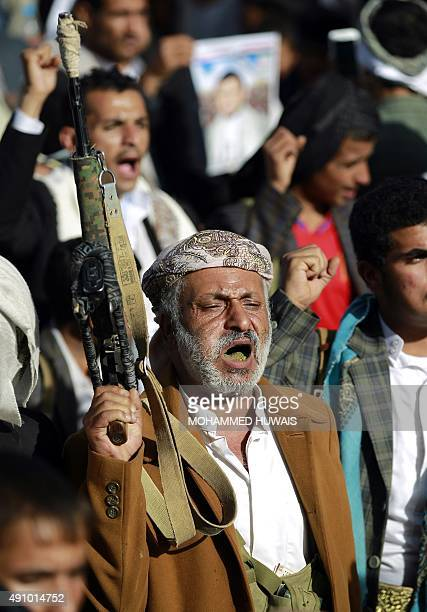 A Yemeni supporter of the Shiite Huthi rebel movement raises his weapon during a protest in the Yemeni capital Sanaa against ongoing military...