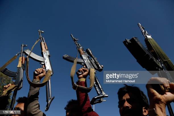 Yemeni supporters of the Houthi group hold up firearms as they protest to reject the Trump administration decision to designate the Houthis, known as...