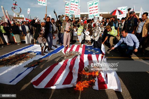Yemeni supporters of the Huthi rebels burn Israeli and US flags as they shout slogans against the United States during an antiUS protest in Sanaa on...