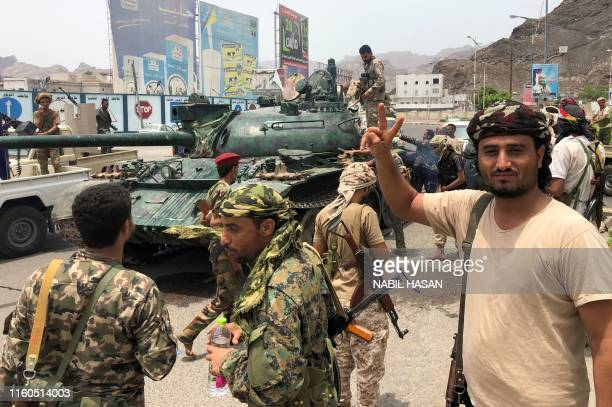 Yemeni supporters of the southern separatist movement pose for a picture with a tank they confiscated from a nearby military base in the southern...