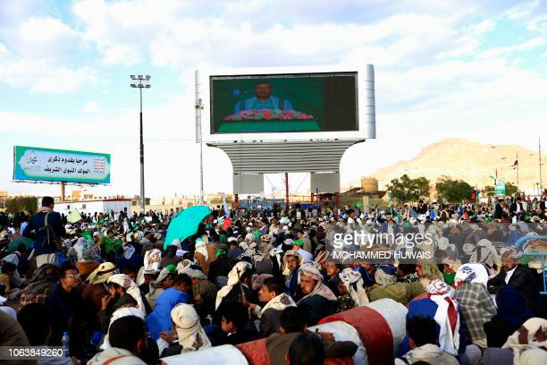 Yemeni supporters to the Shiite Huthi movement watch on a big screen a speech given by leader AbdulMalik alHuthi at a rally marking the birth...