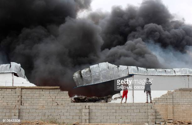 Yemeni take photos of smoke rising from inside a military camp the day after fighters from the separatist Southern Transitional Council took control...