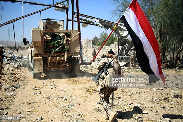 A Yemeni tribesman from the Popular Resistance Committees supporting forces loyal to Yemen's Saudibacked President holds a Yemeni national flag in...
