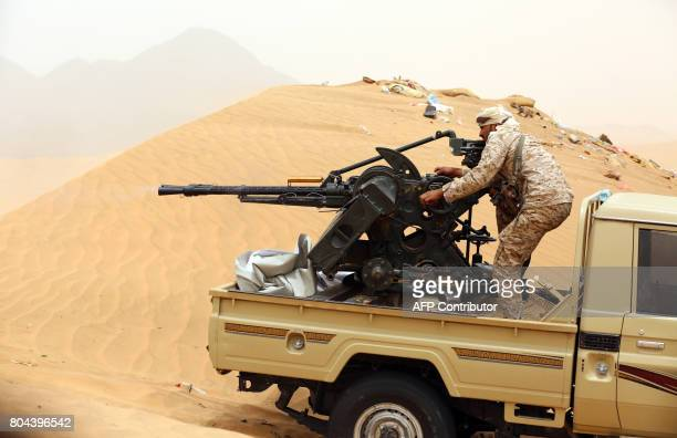 A Yemeni tribesman from the Popular Resistance Committees supporting forces loyal to Yemen's Saudibacked President manoeuvrers a gun mounted on a...