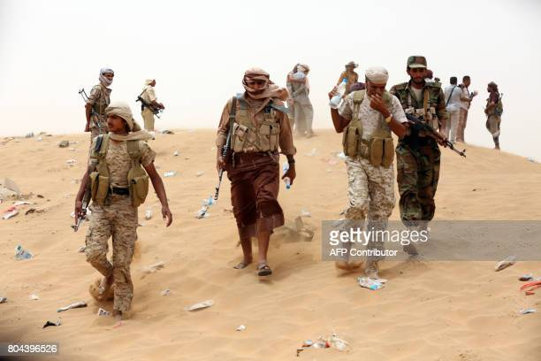 Yemeni tribesmen from the Popular Resistance Committees supporting forces loyal to Yemen's Saudibacked President inspect the area during fighting...