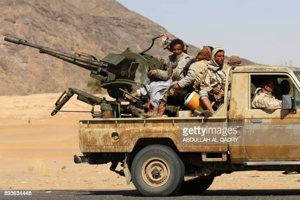Yemeni tribesmen from the Popular Resistance Committees supporting forces loyal to Yemen's Saudibacked President drive through a desert road during...