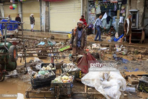 Yemeni vendor looks at goods he managed to salvage from his stall, damaged by floods following heavy rains in the capital Sanaa, on April 14, 2020.