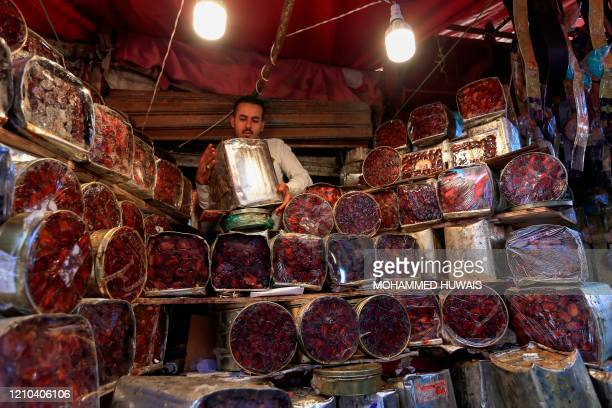 A Yemeni vendor stacks boxes of date in the old city market of the capital Sanaa ahead of the holy Muslim fasting month of Ramadan on April 18 2020...