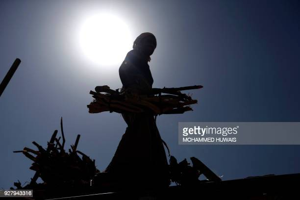 TOPSHOT Yemeni vendors display firewood for sale amid ongoing cooking gas shortages in the Yemeni capital Sanaa on March 6 2018 Yemen is suffering...