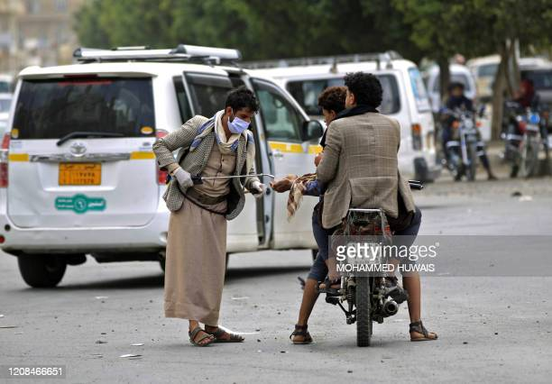 A Yemeni volunteer disinfects the hands of a man driving a motorcycle in the capital Sanaa amid concerns over the spread of the novel coronavirus on...