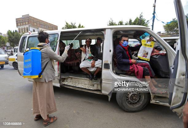 A Yemeni volunteer disinfects the interior of a public transportaion van in the capital Sanaa amid concerns over the spread of the novel coronavirus...