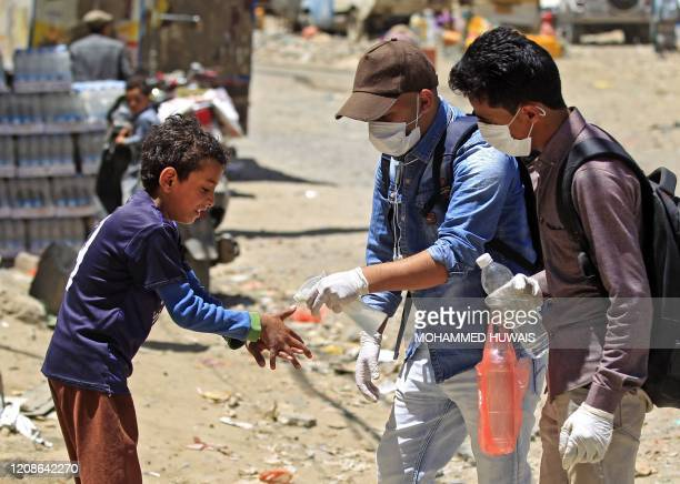 Yemeni volunteer sprays disinfectant on the hands of kid in the one of Sanaa's impoverished neighbourhoods, on March 30 amid concerns of a...