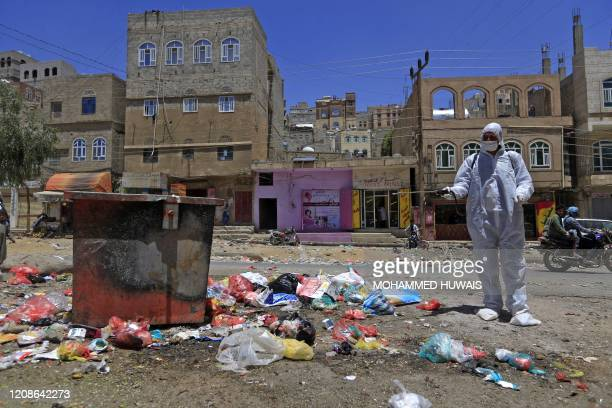 Yemeni volunteer sprays disinfectant over garbage in the one of Sanaa's impoverished neighbourhoods, on March 30 amid concerns of a coronavirus...