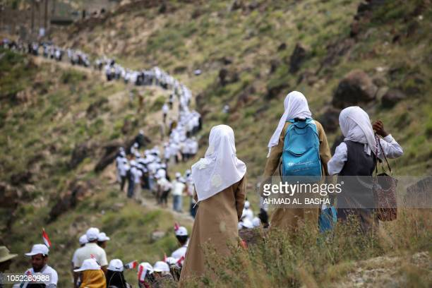 Yemeni volunteers form a human chain to pass food aid supplied by the UAE Red Crescent to mountainous towns on the outskirts of the country's...