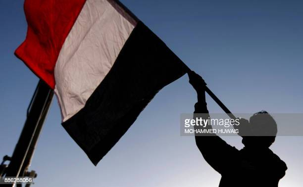 Yemeni waves a national flag during a rally celebrating the death of Yemeni expresident Ali Abdullah Saleh a day after he was killed in the capital...