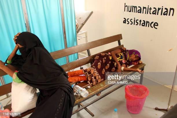 A Yemeni woman accompanies a child believed to be suffering from cholera at a cholera treatment centre in Yemen's northwestern Hajjah province on...