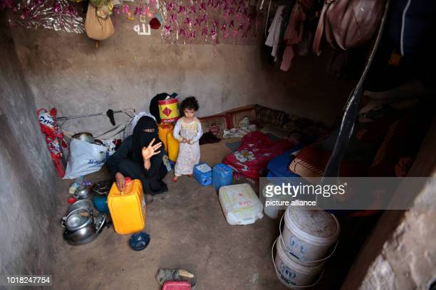 A Yemeni woman and a girl who were displaced from the coastal city of Al Hudaydah sit at a shelter where they live with their family in Sanaa Yemen...