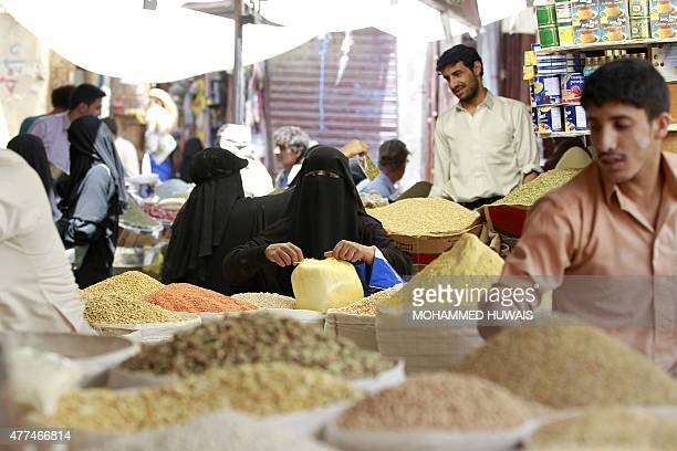 A Yemeni woman does some shopping at a market in the old city of Yemeni capital Sanaa as the faithful prepare for the start of the Muslim holy...